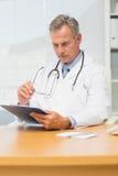 Концентрировать зрелого доктора сидя на его столе с доской сзажимом для бумаги Стоковые Фотографии RF