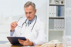 Концентрировать доктора сидя на его столе с доской сзажимом для бумаги Стоковые Изображения RF