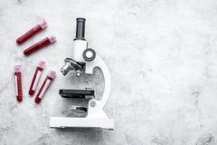 Концепция анализа крови Пробы крови приближают к микроскопу на сером космосе экземпляра взгляд сверху предпосылки Стоковое Фото