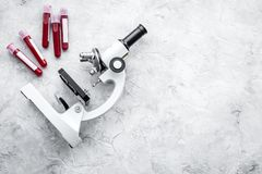 Концепция анализа крови Пробы крови приближают к микроскопу на сером космосе экземпляра взгляд сверху предпосылки Стоковое Изображение