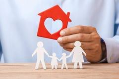 Концепция арендовать дом, кредит или страхование Человек в рубашке держит дом и семья стоит рядом с ним стоковые фото