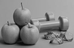Концепция атлетики и веса Рулетка в cyan цвете около штанг и сочных яблок стоковое изображение rf