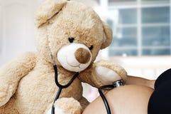 Концепция беременности, медицины и здравоохранения - закройте вверх плюшевого мишки играя стетоскоп доктора и слушайте к ее матер стоковое фото