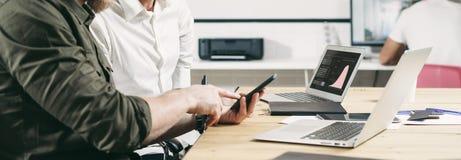 Концепция бизнесменов коллективно обсуждать Бородатая рука pointinh человека на экране мобильного телефона широко стоковые фотографии rf