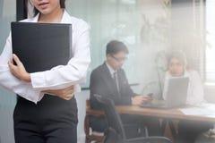 Концепция бизнес-леди руководства Уверенно молодая азиатская коммерсантка при связыватель кольца стоя против ее коллеги в офисе b стоковая фотография