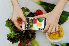 Концепция блоггера еды Руки с изображениями конца-вверх телефона еды Стоковое Изображение RF