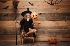 Концепция ведьмы хеллоуина - без сокращений съемка маленького кавказского ребенка ведьмы представляя с волшебным broomstick над л Стоковая Фотография