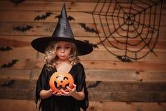 Концепция ведьмы хеллоуина - маленький кавказский ребенок ведьмы разочаровывая без конфеты в опарнике тыквы конфеты хеллоуина над стоковое изображение