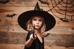 Концепция ведьмы хеллоуина - маленький ребенок ведьмы наслаждается сыграть с волшебной палочкой над предпосылкой летучей мыши и с стоковое изображение