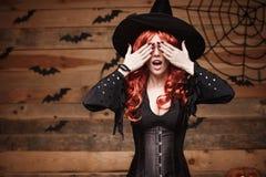 Концепция ведьмы хеллоуина - счастливая ведьма волос хеллоуина красная держа руки закрывая глаза представляя над старой деревянно Стоковые Изображения RF