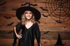 Концепция ведьмы хеллоуина - съемка крупного плана маленького кавказского счастливого ребенка ведьмы представляя над предпосылкой Стоковая Фотография