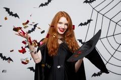 Концепция ведьмы хеллоуина - confetti счастливой элегантной ведьмы бросая для праздновать партию хеллоуина над летучей мышью и па стоковые изображения