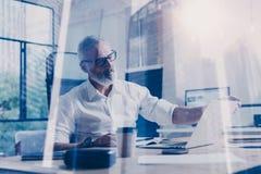 Концепция взрослого бородатого бизнесмена нося классические стекла и работая на деревянной таблице с компьтер-книжкой в современн Стоковая Фотография RF