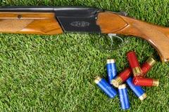Концепция винтовки и патронов звероловства на траве Стоковые Изображения