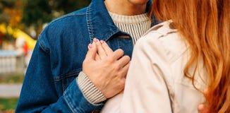 Концепция влюбленности, отношения, семьи и людей - близкая вверх пар рука ` s девушки лежит на плече ` s парня, человеке держит е стоковые изображения