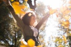 Концепция влюбленности, отношения, семьи и людей - усмехаясь женщина в парке осени среди желтых листьев стоковые фотографии rf