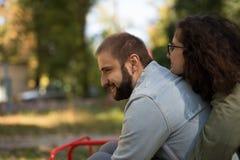 Концепция влюбленности, отношения, семьи и людей - усмехаясь пары в осени паркуют среди желтых листьев имея потеху стоковое изображение rf