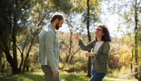 Концепция влюбленности, отношения, семьи и людей - усмехаясь пары в осени паркуют среди желтых листьев имея потеху стоковая фотография