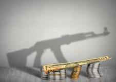 Концепция войны финансирования, деньги с тенью оружия стоковое фото rf