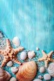 Концепция временени с seashells и морскими звёздами на голубых деревянных досках Остатки на пляже Предпосылка с космосом экземпля Стоковая Фотография RF