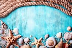 Концепция временени с seashells и морскими звёздами на голубых деревянных досках Остатки на пляже Предпосылка с космосом экземпля Стоковое фото RF