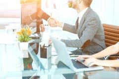 Концепция выгодских партнерств - рукопожатие деловых партнеров на предпосылке настольного компьютера Стоковое Изображение