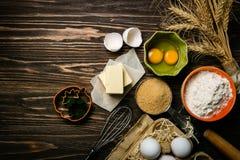 Концепция выпечки - ингридиенты выпечки умаслят, flour, засахаривают, яичка на деревенской деревянной предпосылке стоковое фото