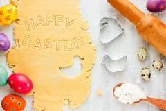 Концепция выпечки пасхи: сырцовое тесто для печенья, красочных яичек Стоковые Фотографии RF