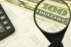 Концепция вычисления дохода Увеличитель увеличивает деноминацию 100 долларов на предпосылке номеров Стоковая Фотография