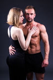 Концепция влюбленности и спорта - сексуальная женщина и мышечный человек над серым цветом Стоковое Фото