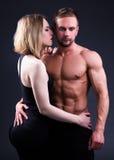 Концепция влюбленности и спорта - сексуальная sporty пара обнимая над серым цветом Стоковые Фотографии RF