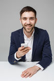 Концепция дела - бизнесмен портрета красивый счастливый красивый в костюме играя телефон moblie и усмехаясь с компьтер-книжкой на Стоковое Фото