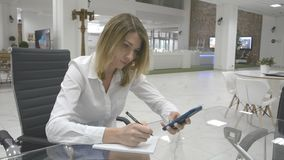 Концепция дела: бизнес-леди принимает примечания от телефона сток-видео