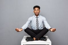 Концепция дела - портрет Афро-американского бизнесмена делая раздумье и йогу внутри перед работой Стоковые Изображения RF