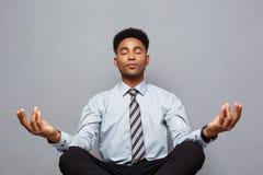 Концепция дела - портрет Афро-американского бизнесмена делая раздумье и йогу внутри перед работой стоковая фотография rf