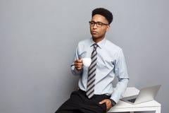 Концепция дела - портрет Афро-американского бизнесмена имея кофе сидя на столе используя компьтер-книжку Стоковое Изображение RF