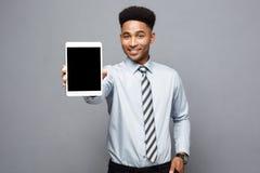 Концепция дела - счастливый красивый профессиональный Афро-американский бизнесмен показывая цифровую таблетку к клиенту стоковые фотографии rf