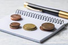 Концепция дела, финансов или вклада Монетки, чековая книжка или тетрадь и авторучка деревянное предпосылки белое стоковые фото