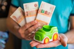 Концепция дела, финансов, сбережений, банка или автокредита Миниатюрная модель автомобиля в руке, деньгах и банковской книжке на  стоковое изображение rf
