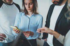 Концепция деловой встречи сотрудников Молодые женщины держа руку мобильного телефона и новости обсуждения с ее коллегами стоковое фото