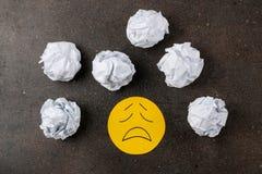 Концепция депрессии Психологическая болезнь грустный smiley и скомканные бумажные ширины на темной предпосылке Взгляд сверху стоковое изображение