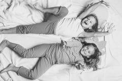 Концепция детства и счастья Дети с усмехаясь сторонами лежат дальше и держат руки вверх Стоковая Фотография