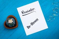 Концепция Де-стресса напоминания мотивационная на таблице белой бумаги и сини Стоковое Фото