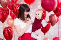Концепция дня Валентайн - счастливая красивая женщина с дочерью над красной предпосылкой воздушных шаров стоковое изображение rf