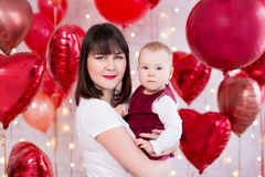 Концепция дня Валентайн - счастливая красивая женщина с дочерью над красной в форме сердц предпосылкой воздушных шаров стоковое фото