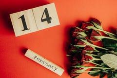 Концепция дня валентинок St минимальная на красной предпосылке Красные розы и деревянное caledar с 14-ое февраля на ем Стоковое Изображение