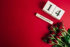 Концепция дня валентинок St минимальная на красной предпосылке Красные розы и деревянное caledar с 14-ое февраля на ем Стоковые Изображения