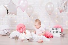 Концепция дня рождения - маленькая девочка с тортом над предпосылкой кирпичной стены со светами и воздушными шарами стоковые фото