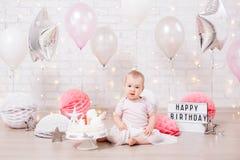 Концепция дня рождения - счастливая маленькая девочка с тортом над предпосылкой кирпичной стены со светами и воздушными шарами стоковая фотография rf