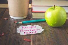 Концепция дня учителя Объекты на предпосылке доски Книги, зеленое яблоко, металлическая пластинка: День, карандаши и ручки счастл стоковое фото